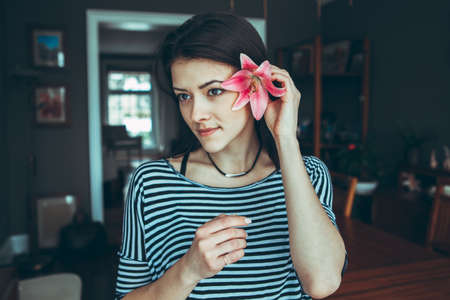 Closeup portrait of smiling pensive Caucasian young beautiful woman model with long hair in striped t-shirt holding large pink flower near ear hair, looking away, toned with filters