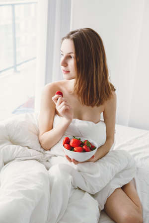 Portrait of smiling beautiful young Caucasian woman with long hair sitting in bed early morning by window, eating red fresh strawberry, lifestyle, toned with filters