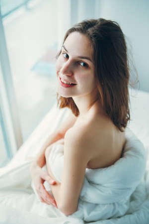 Close up portrait of smiling young beautiful Caucasian woman sitting in bed after waking up, indoors at home early morning, lifestyle, toned with filters Foto de archivo