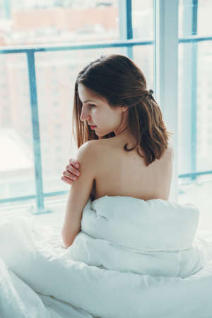 Back view of young Caucasian woman with long hair sitting in bed by window after waking up, indoors at home early morning, lifestyle, toned with filters
