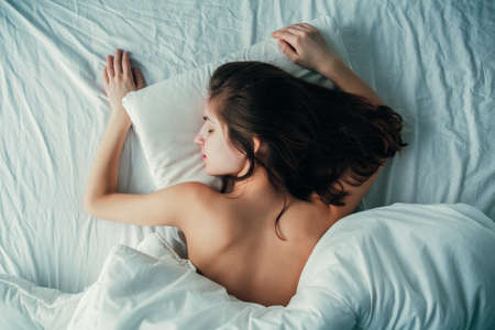 Portrait of young white Caucasian woman lying in bed sleeping, her messy hair on pillow, indoors at home early morning, lifestyle, toned with filters, view from top above Foto de archivo