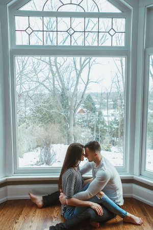 Portrait of beautiful romantic young couple man woman in love hugging, kissing, indoors at home sitting by large arch window, toned with filters, authentic lifestyle Foto de archivo