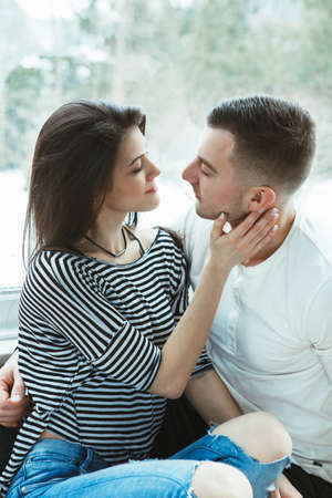 Portrait of beautiful romantic young couple man woman in love, indoors at home sitting by window looking at each other, touching face neck cheek, toned with filters, authentic lifestyle