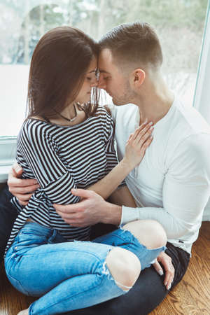 Portrait of beautiful romantic young couple man woman in love hugging, indoors at home sitting by window, toned with filters, authentic lifestyle Foto de archivo
