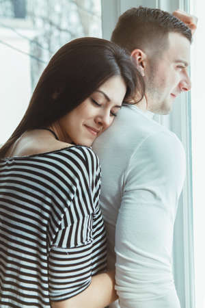 Closeup portrait of beautiful romantic young Caucasian couple man woman in love hugging, indoors at home standing by window, toned with filters, authentic lifestyle Foto de archivo