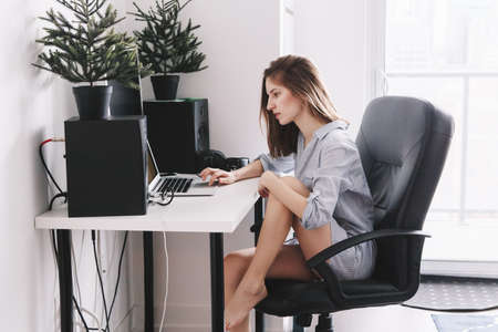 Portrait of young beautiful Caucasian girl woman student in pajamas shirt  working on laptop computer sitting in office chair at home, browsing internet, drinking coffee, early morning lifestyle