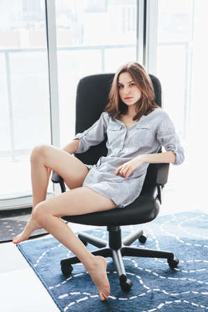 Portrait of young beautiful sexy Caucasian woman with long hair dressed in pajamas shirt, sitting in office chair at home, looking in camera, lazy early morning lifestyle