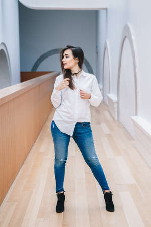 untidy: Portrait of smiling white Caucasian brunette young beautiful girl woman model with long dark hair in white shirt and blue jeans indoor in hall of college, university, standing full figure looking away