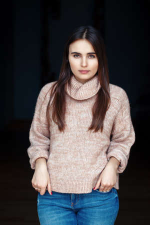 Portrait of pensive sad serious white Caucasian brunette young beautiful girl woman model with long dark hair and brown eyes in turtleneck sweater and blue jeans indoor on black background