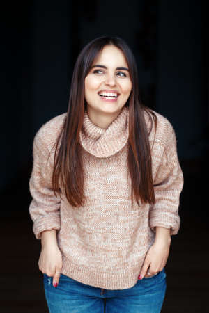 Portrait of smiling laughing white Caucasian brunette young beautiful girl woman model with long dark hair and brown eyes in turtleneck sweater and blue jeans indoor on black background