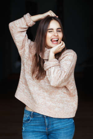 Portrait of funny white Caucasian brunette young beautiful girl woman with long dark hair in turtle sweater and blue jeans indoor on black background, smiling laughing showing her tongue