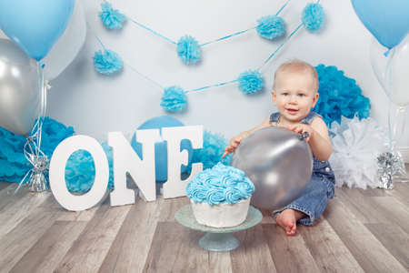 Portrait of cute adorable blond Caucasian baby boy with blue eyes in jeans overall, holding grey balloon, celebrating his first birthday, letters word one, cake smash in studio Foto de archivo