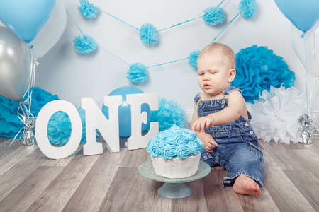 Portrait of cute adorable blond Caucasian baby boy with blue eyes in jeans overall, celebrating his first birthday with gourmet cake, letters one and balloons, cake smash in studio Foto de archivo
