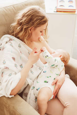 Portrait of young beautiful middle age blonde Caucasian mother holding breastfeeding baby sitting in armchair covered with blanket linen sheet