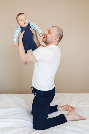 family tickle: Portrait of middle age Caucasian father in white t-shirt and black jeans sitting on bed indoors, holding taking up newborn baby son making him laugh, funny touching real lifestyle