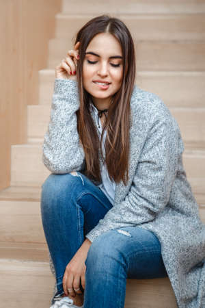 untidy: Portrait of pensive Caucasian brunette young beautiful girl woman with long dark hair and brown eyes in white shirt, grey coat and blue jeans sitting on staircase looking down