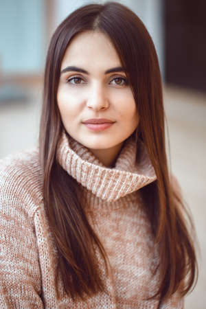 Closeup portrait of pensive white Caucasian European brunette young beautiful woman model with long dark red hair and brown eyes in turtleneck sweater, looking in camera