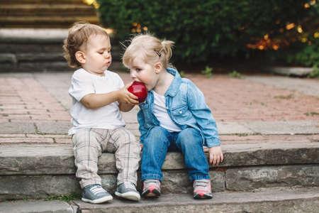 Groepsportret van twee witte Kaukasische leuke aanbiddelijke grappige kinderentoddlerers die samen het delen van het eten van appelvoedsel zitten, houd voor altijd van het concept van de vriendschapsjonge geitjes, beste vrienden