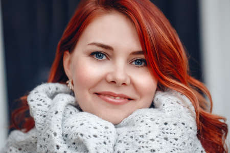 Closeup portrait of smiling middle aged white caucasian woman with waved curly red hair in knitted scarf shawl, looking in camera,outside park, beauty fashion lifestyle concept