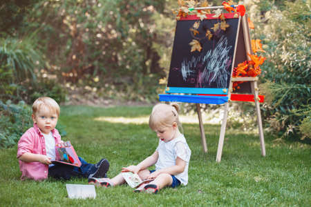 Group of two white Caucasian toddlers children kids, boy and girl sitting in grass outside by drawing easel with books reading studying learning, back to school concept, summer autumn