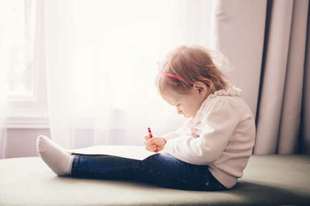 Portrait of cute adorable white Caucasian little girl drawing with pencil on paper, sitting on couch indoor, looking serious concentrated,  lifestyle childhood early development