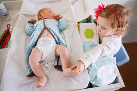Lifestyle portrait of  cute girl toddler helping her mother, changing baby diaper. Older sister looking at her little younger sibling brother.