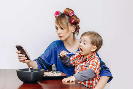 Busy tired white Caucasian young woman mother housewife with hair-curlers in hair looking on phone, surfing Internet,  funny child son boy sitting eating meal lunch, white background