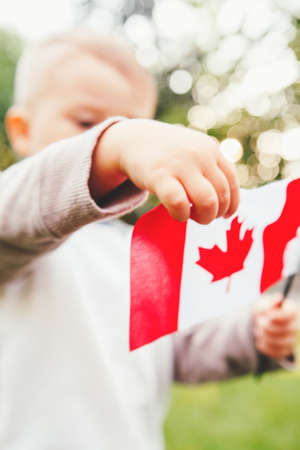 Closeup portrait of little blond Caucasian boy child hand holding Canadian flag with red maple leaf  in park outside celebrating Canada Day Stock Photo