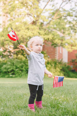 Happy adorable little blond Caucasian girl holding waving American and Canadian flag in park outside celebrating 4th july Independence Day, Canadian Day, friendship support Stock Photo