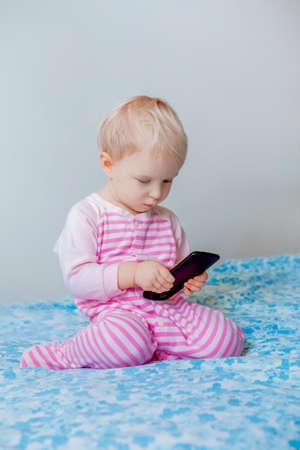 かわいい愛らしい白い白人金髪の赤ちゃんの顔、ライフ スタイル新世代技術、初期開発の面白い表現でモバイルの携帯電話での再生呼び出しを行う 写真素材