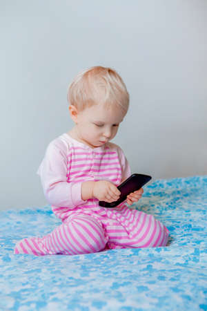 Cute adorable white Caucasian blond baby making a call, playing with mobile cell phone with funny expression on face, lifestyle new generation technology, early development