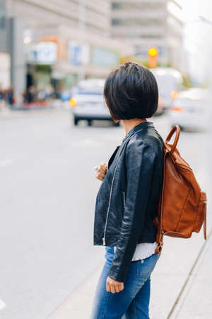 Portrait of young girl woman with short dark hair bob style, in blue jeans and leather biker jacket, with yellow brown backpack on shoulder, standing in city street, view from back behind Foto de archivo