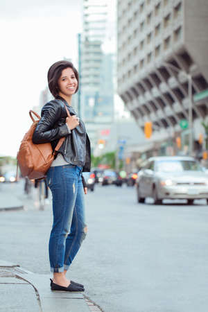 Portrait of smiling laughing beautiful young hispanic latin girl woman with short dark hair in blue jeans and leather biker jacket, holding backpack, standing in city street, ethnic diversity