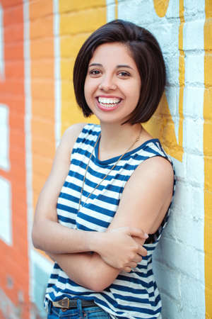 Portrait of beautiful smiling young hipster latin hispanic girl woman with short hair bob in striped tshirt leaning on red brick wall in city looking in camera, ethnic diversity lifestyle