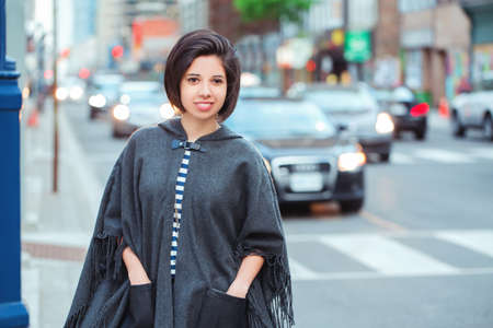 Closeup portrait of beautiful smiling young latin hispanic girl woman with short dark black hair bob, outside in busy street with cars,  natural smile emotion, ethnic diversity
