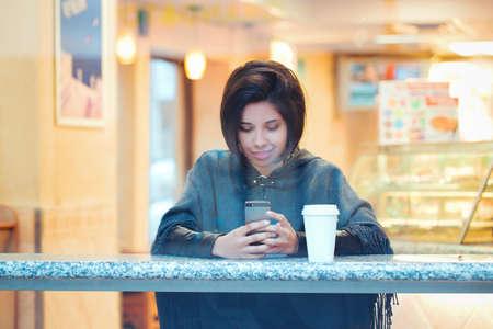 Candid retrato de la joven y bella hispanos latina mujer hispana chica con pelo corto bob en la chaqueta de poncho de cabo gris sentado en el restaurante de la cafetería con café mirando a otro lado disparó a través de la ventana Foto de archivo