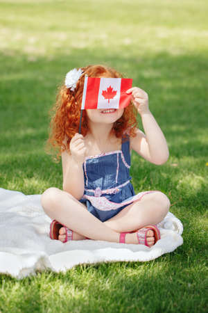 Portret van leuk klein roodharig Kaukasisch meisjeskind die Canadese vlag met rood esdoornblad houden, zittend op gras in park buiten, vierend de Dag van Canada verjaardag