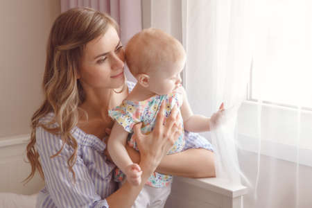 Closeup portrait of beautiful white Caucasian woman mother with cute adorable blonde baby girl daughter with large blue eyes, sitting on bed near window together, candid family lifestyle