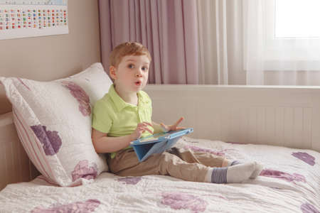 Portrait of cute adorable white Caucasian toddler boy sitting in bed playing with digital tablet with funny face expression, candid lifestyle, early development, new technology generation
