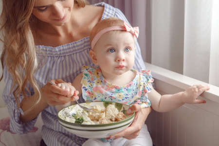 Closeup portrait of young woman mother trying to feed her baby girl daughter with vegetables, broccoli, cauliflower, healthy organic food for child, candid lifestyle family life Stock Photo