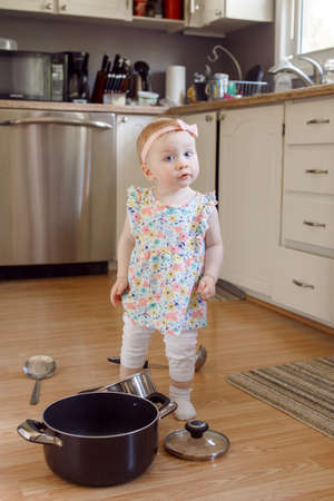 Portrait of cute adorable funny little Caucasian blonde baby girl playing in kitchen with utensils, pot and ladle, child with funny face emotional expression, happy childhood concept