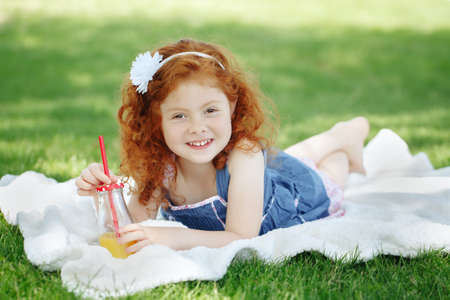 Portrait of cute adorable little red-haired Caucasian girl child in blue dress laying on grass in park outside drinking orange juice from glass bottle, happy lifestyle childhood concept