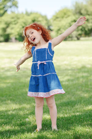 Portrait of cute adorable little red-haired Caucasian girl child in blue dress standing in field meadow park outside playing singing having fun, happy lifestyle childhood concept Stok Fotoğraf