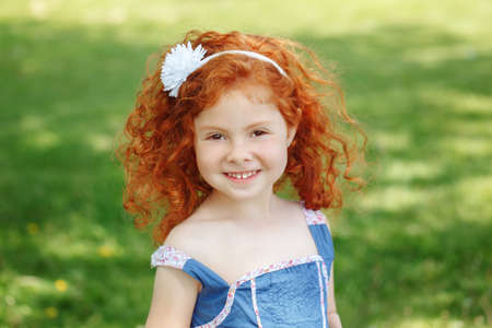 Closeup portrait of cute adorable little red-haired Caucasian girl child in blue dress standing in field meadow park outside looking in camera, happy lifestyle childhood concept