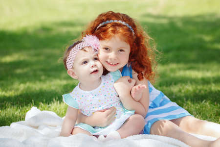Portrait of two cute adorable little red-haired Caucasian girls sisters siblings children, sitting together in field meadow park outside, hugging, looking in camera, happy lifestyle childhood concept