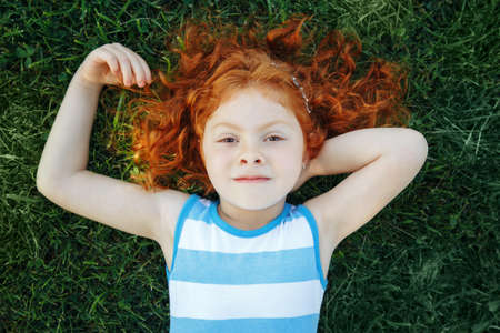 Portrait of cute adorable pensive little red-haired Caucasian girl child in blue dress lying  on green grass in park outside dreaming thinking, happy lifestyle childhood concept, view from above