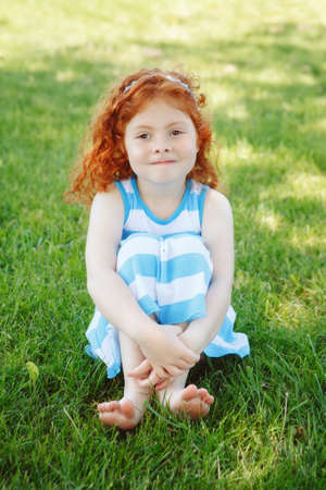 Portrait of cute adorable little red-haired Caucasian girl child in blue dress sitting in field meadow park outside looking in camera, having fun, happy lifestyle childhood concept
