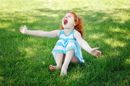 Portrait of cute adorable little red-haired Caucasian girl child in blue dress sitting on grass in park outside playing singing crying desperately, having fun, happy lifestyle childhood concept Foto de archivo
