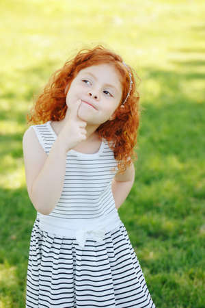 Portrait of cute adorable puzzled little red-haired Caucasian girl child in white striped dress standing in field meadow park outside thinking, having fun, happy lifestyle childhood concept