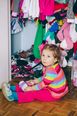 Portrait of cute adorable  little white Caucasian girl baby sitting on floor in wardrobe, wearing shoes, funny emotional face expression, lifestyle authentic childhood concept